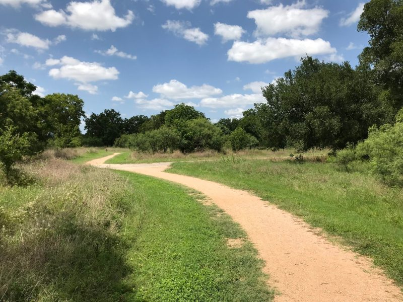 A gravel trail winds through woods and prairie at Crescent Bend Nature Park.