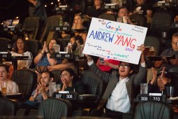 Mateo Lopez waves a sign in support of Andrew Yang.