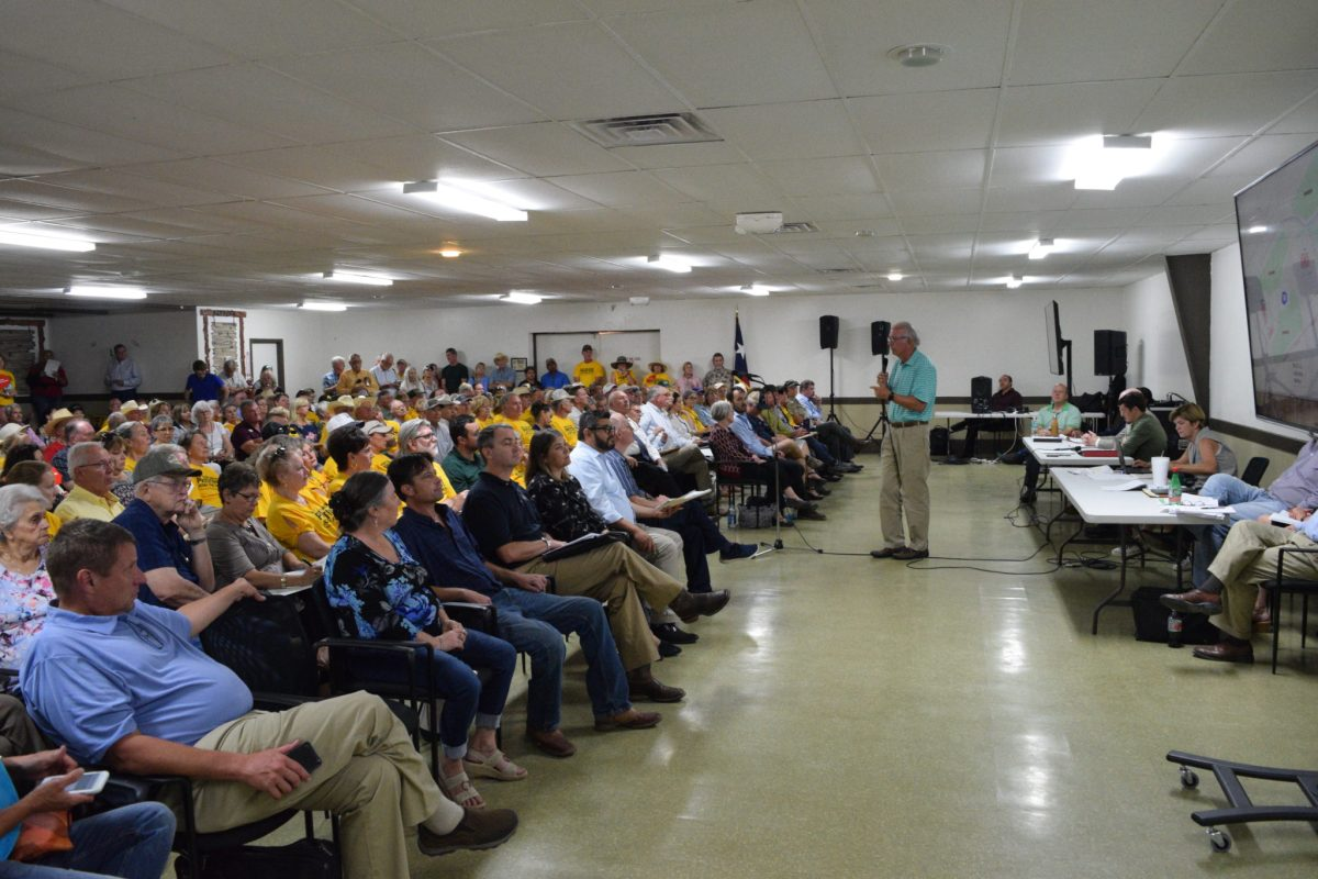 Christian youth camp owner Sam Torn speaks to a crowded hall in Bandera about a permit request underway to discharge treated sewage effluent to Commissioners Creek.