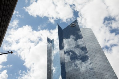 Clouds are reflected by the Frost Tower, as seen from Houston Street.