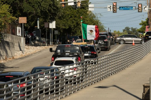A truck drives to the Alamodome with a Mexican flag attached to the back.