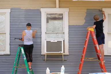 Elizabeth Argubright and her son Rocco paint a home in the Mission Historic District.