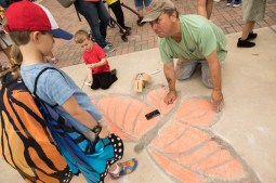 Artist Tim Olson draws a monarch butterfly in front of the Pearl Food Hall.