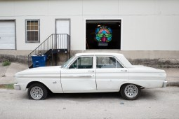 A Ford Futura is parked in front of a craneos skull in progress by muralist Shek Vega.