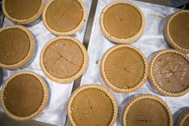 Pumpkin pies are sliced before being served to attendees.