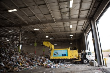 A City of San Antonio truck drops recyclables on the building's floor in preparation for the sorting process.