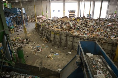 Recyclables to be sorted pile up on the floor of a Republic Services building.