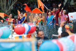 Participants representing the state of Maharashtra wave flags and greet the audience during the river parade.
