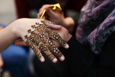 Henna tattoo artists decorate the hands and arms of Diwali attendees.