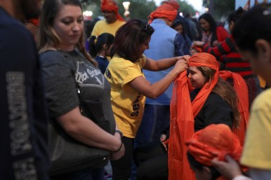 Volunteers of Sewa International wrap traditional safas on attendees during Diwali.