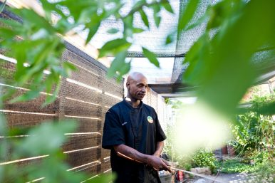 Gus Bard, the chef and creator of Sweet Yams' unique menu, waters the plants on the back patio after the restaurant closed for the day.