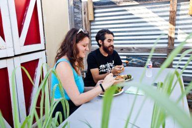 Bethany Overzat, left, and Cloud Naranjo enjoy a salad and lemon garlic salmon on the back patio of the Sweet Yams restaurant.