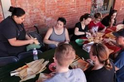 Edna Arteaja from Viva Villa demonstrates how to spread masa on the corn hush.