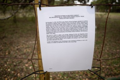 Public notices of the creation of a water supply district are posted on property fences along County Road 424 in Medina County.