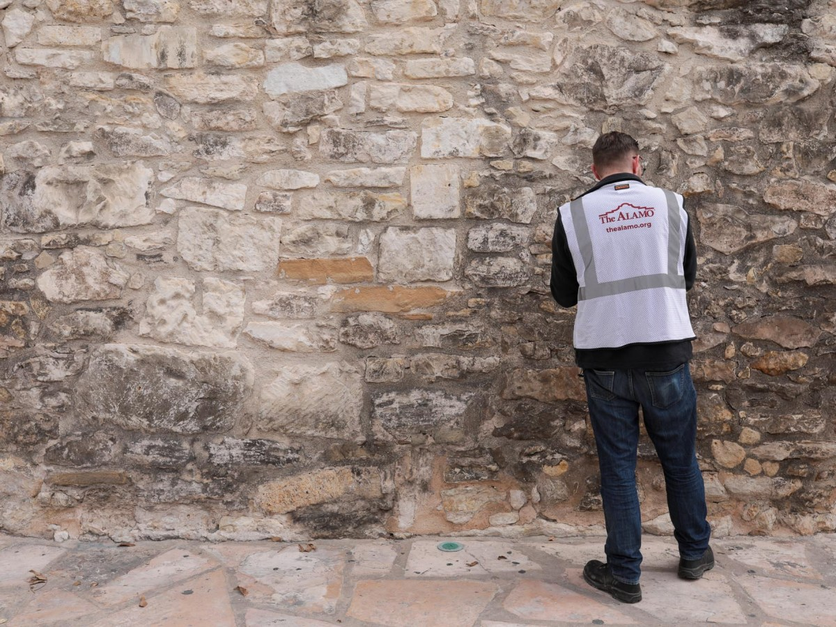 A surveyor examines the Long Barracks walls at the Alamo in October 2019.