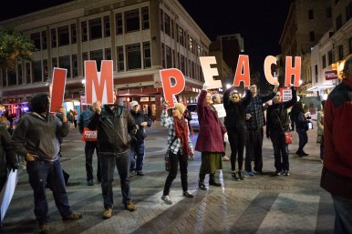 """A group of seven people hold letters that spell out """"impeach"""" during the rally."""