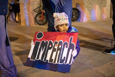 """A young girl holds a sign that reads """"impeach"""" next to the Federal Building and U.S. Courthouse."""