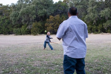 Cade, 8, and Mike Benavidez play catch in the front yard.