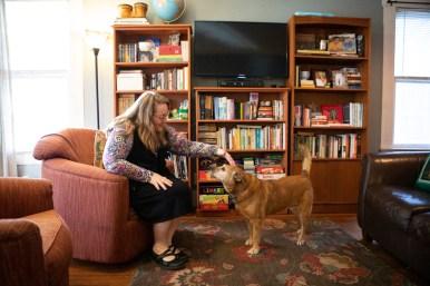 Mitzi Moore pets her dog Bella in her living room.