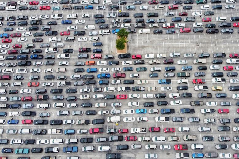 "An aerial view of the San Antonio Food Bank's ""mega distribution"" site Friday shows vehicles lined up by the hundreds in the Alamodome parking lot to pick up two weeks' worth of groceries."