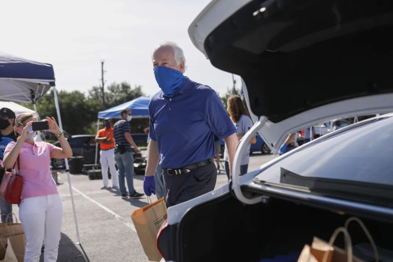 U.S. Sen. John Cornyn (R-Texas) loads bags of groceries into vehicles during a San Antonio Food Bank distribution at the Alamodome.