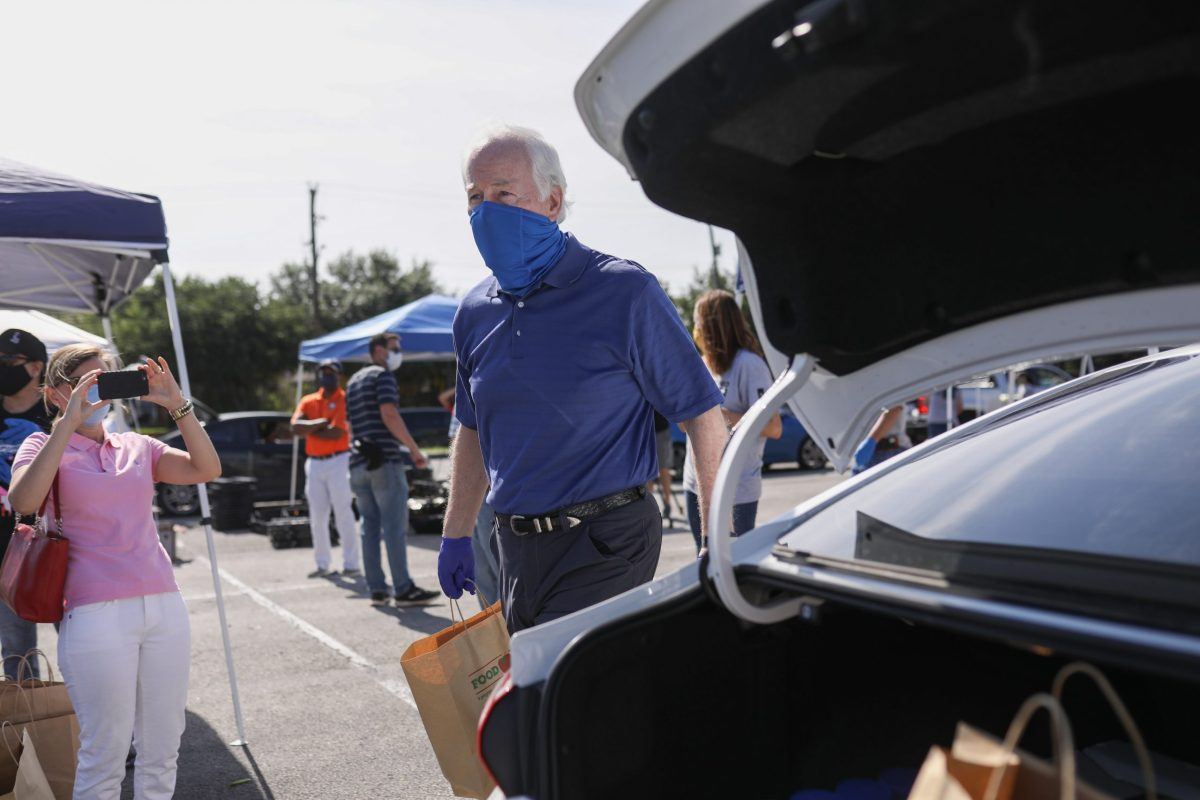 U.S. Sen. John Cornyn (R-Texas) loads bags of groceries into vehicles during a San Antonio Food Bank distribution at the Alamodome.
