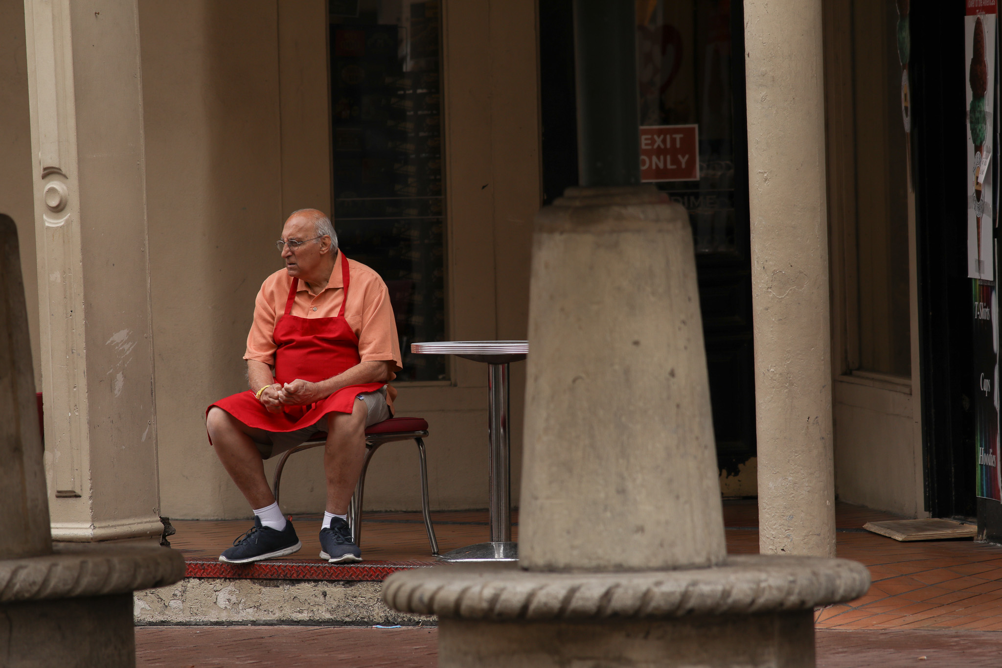 A business owner sits outside his store in Alamo Plaza as the coronavirus and rainy weather have slowed downtown foot traffic.