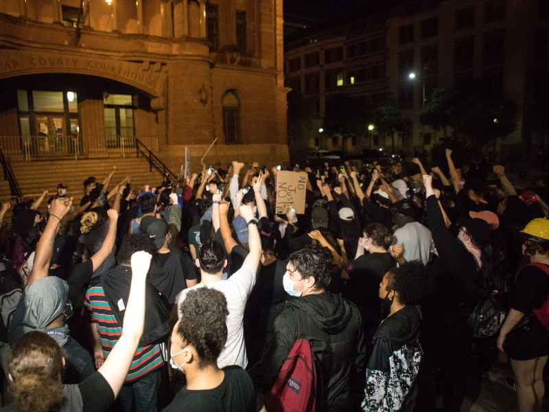 Protesters in the local demonstrations against police brutality raise their fists in front of the Bexar County Courthouse on Tuesday night.