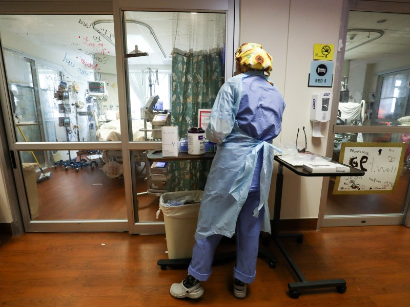 A nurse at the Methodist Hospital COVID-19 ICU checks on a patient through the glass doors of the room.