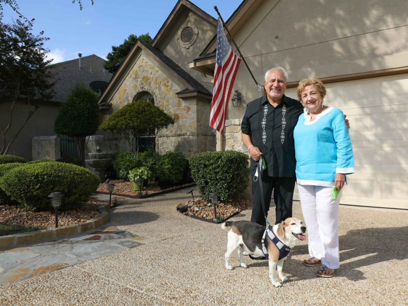Joe Jesse and Minnie Sanchez stand in front of their home in the Emerald Forest neighborhood in North San Antonio.
