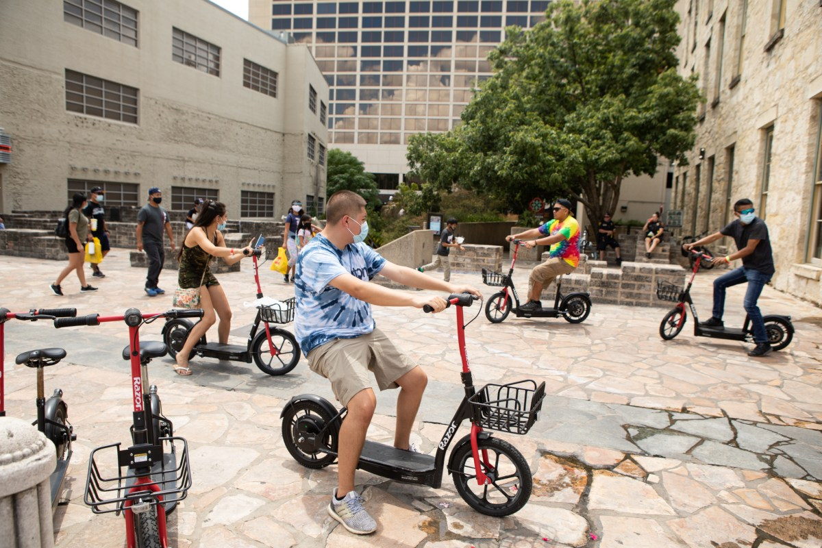 People ride scooters through Alamo Plaza, some wearing masks, as tropical storm Hanna makes its way to the Texas Coast.