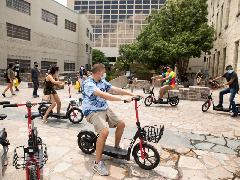 People ride scooters through Alamo Plaza, and only some wear masks in summer 2020.