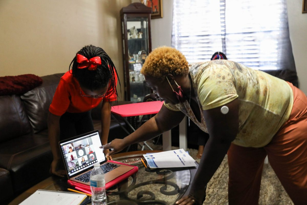 Yolanda Davis (right) works with her daughter Kandis, 12, on technical issues she's experiencing in a virtual learning classroom at IDEA Eastside.