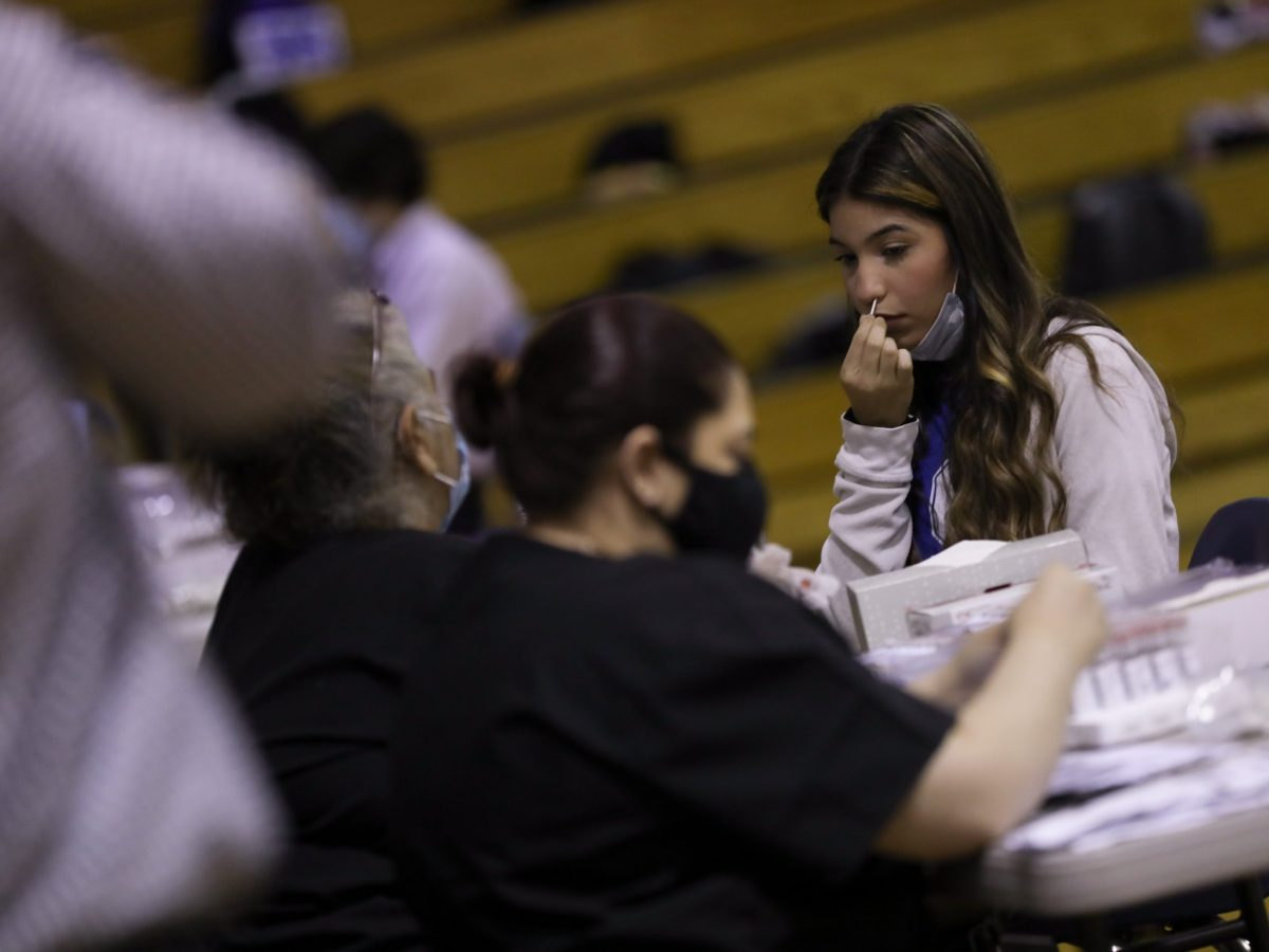 Student Monique Perez, a sophomore at Somerset High School, swabs her nose to test for the coronavirus in the gymnasium.