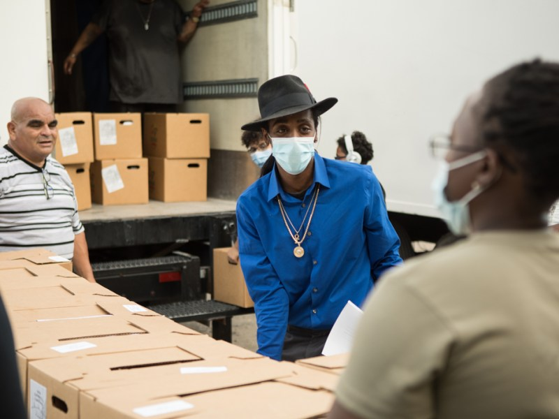 Pharaoh Clark, center, founder of Uniting America Outreach, organizes boxes to hand out to marginalized families.
