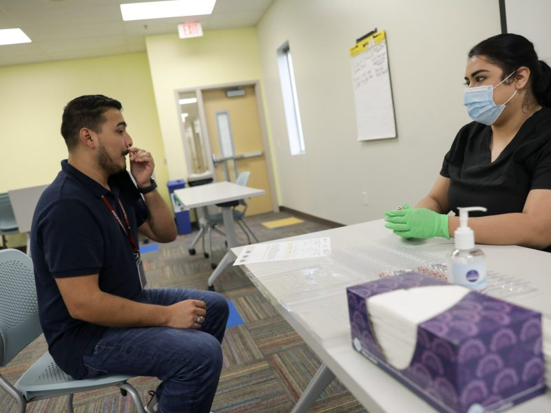 Ruben Betancourt, left, self-administers a rapid COVID-19 test facilitated by Community Labs.