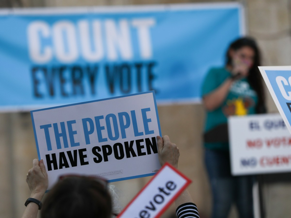 Signs in support of democracy are held up during the Texas Organizing Project's Wednesday rally.