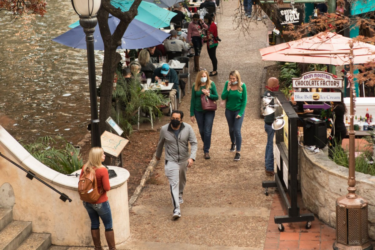 Crowd of people (some wearing masks, some not) gather on the River Walk downtown during the coronavirus pandemic. Photos taken on December 23, 2020.