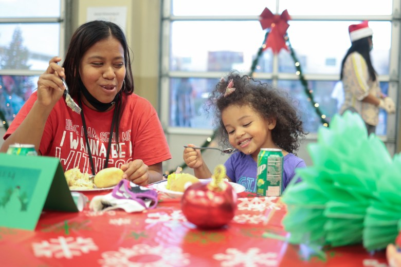 Sarah Smith enjoys dinner with her daughter, Joleah, 3, at the Haven for Hope campus annual Ho Ho Hope for the Holidays celebration.