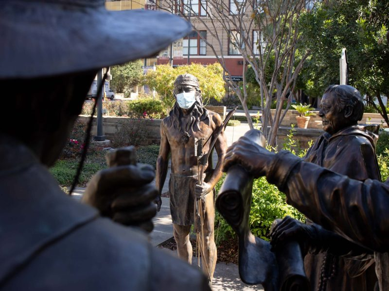 """One of the sculptures that make up the Founders Monument at the Bexar County Courthouse """"wears"""" a mask Jan. 15."""