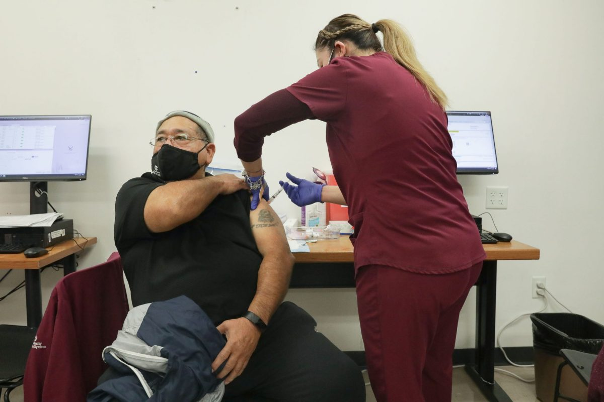 Jesus Perales is injected with a dose of the Moderna COVID-19 vaccine.