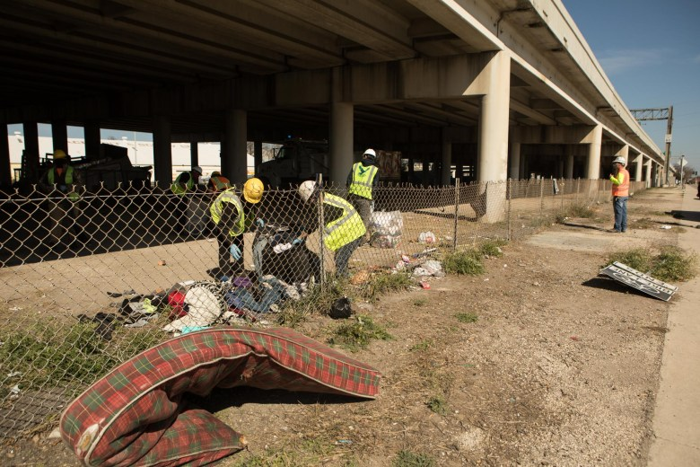 Police officers and homeless outreach teams clean up an encampment under Interstate 37 near Brooklyn Avenue. Photos taken on February 3, 2021.