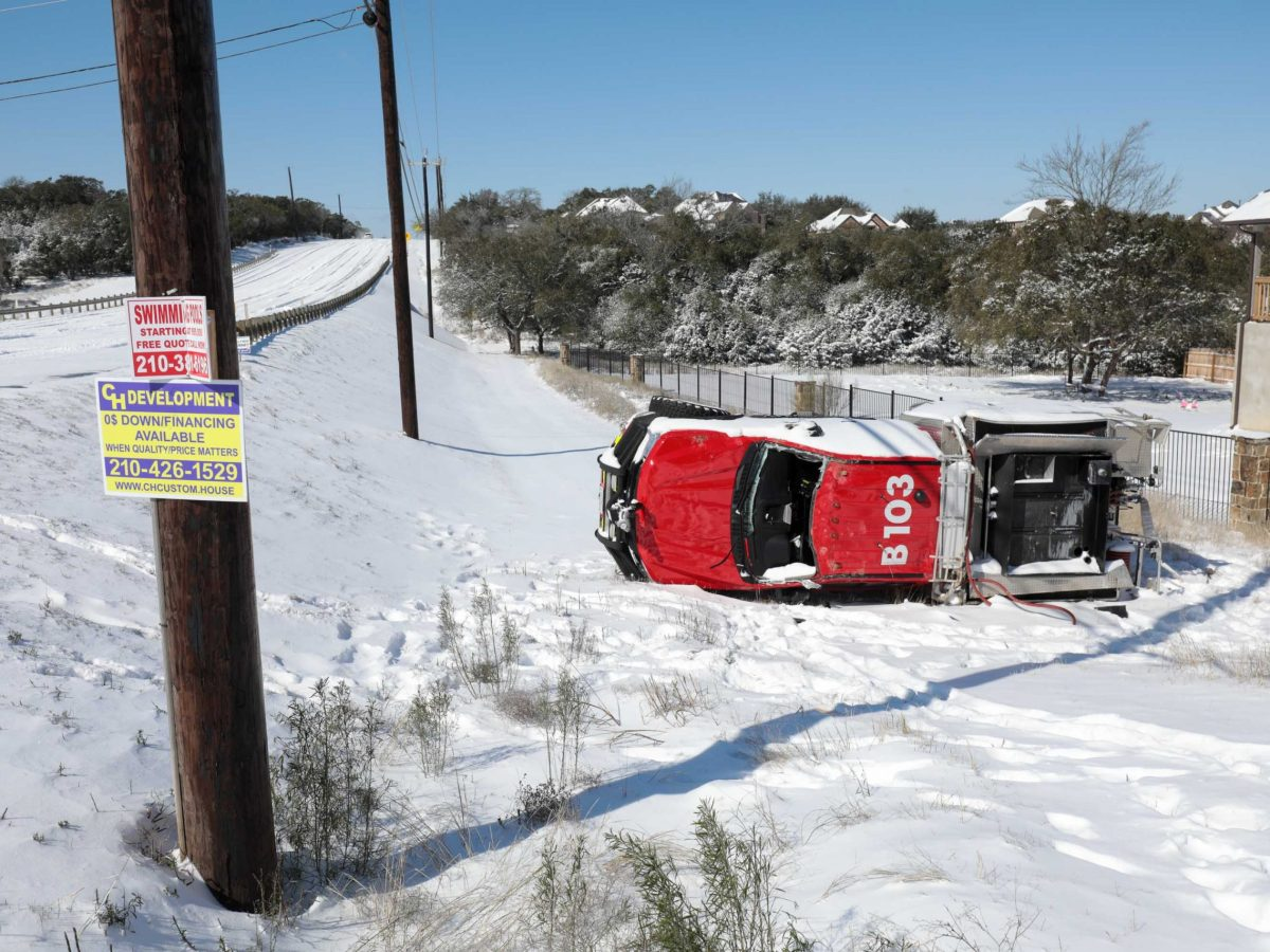 A Bexar County emergency vehicle involved in a rollover lies on a ditch off Borgfeld Drive on Feb. 15.