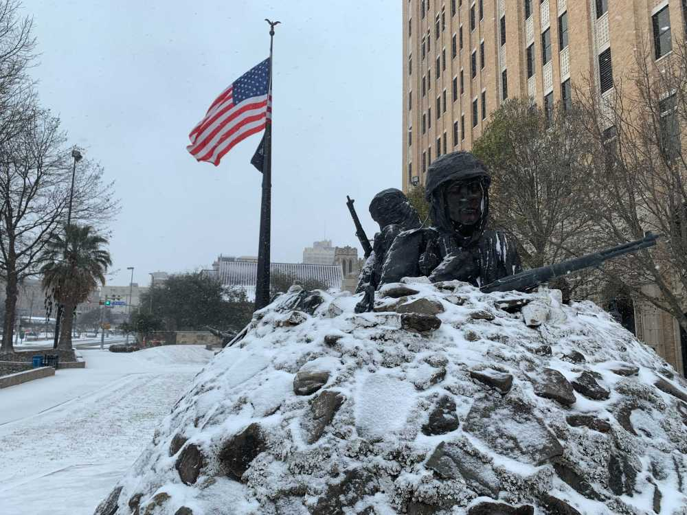 Snow falls on the sculptures at Veterans Memorial Park on Thursday morning.