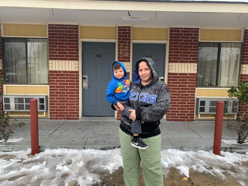 Krystal Vital stands with her 5-year-old son outside of the Alamo Inn & Suites on Commerce Street.