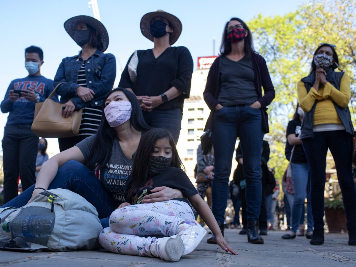 Minh Nguyen and five-year-old Leila Marroquin sit while listening to speakers at the Stop Asian Hate vigil on Saturday.