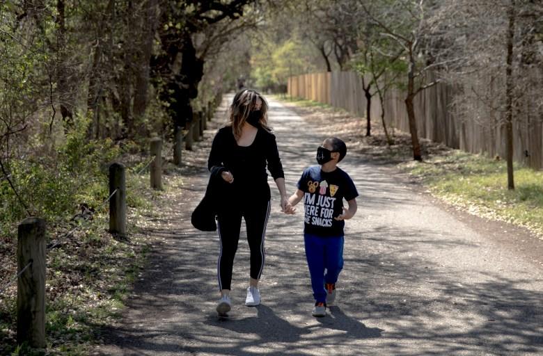 Iris Nuno walks with her 6-year-old son, Jared, along the Salado Creek Greenway on Saturday in San Antonio.