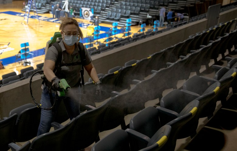 Belinda Taylor cleans spectator seats with an electrostatic sprayer after a college basketball game between Oklahoma State and Wake Forest in the first round of the women's NCAA tournament at St. Mary's University on Sunday in San Antonio.