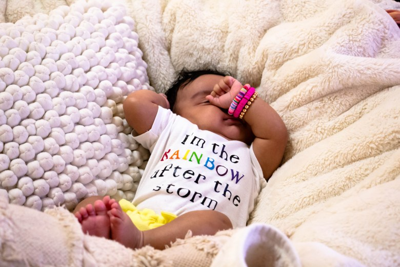 "Five-month-old Raya Linda Aguilera weighed only three pounds when she was delivered by a team of doctors and nurses in the COVID-19 ICU unit of Methodist Hospital. She wears a onesie that says, ""I'm the rainbow after the storm."""