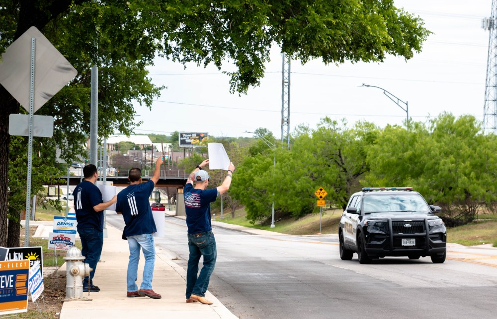 Three men who are holding signs encouraging voters to vote against Prop B wave to a passing police car who honked back at them. They are outside of the polling place housed inside of the Claude Black Center.